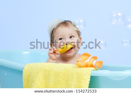 adorable baby boy taking bath in blue tub - stock photo