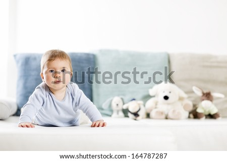 Adorable baby boy with blue eyes in blue shirt lying on belly on sofa and looking straight, blurred toys in background. - stock photo