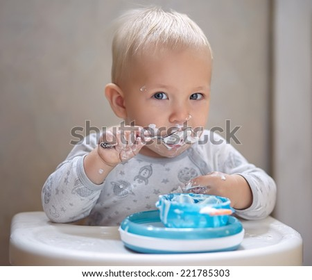 Adorable Baby Boy with Dirty Face Eating Yogurt - stock photo