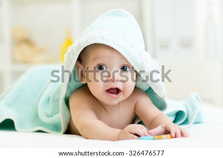 Adorable baby child under a hooded towel after bathing - stock photo