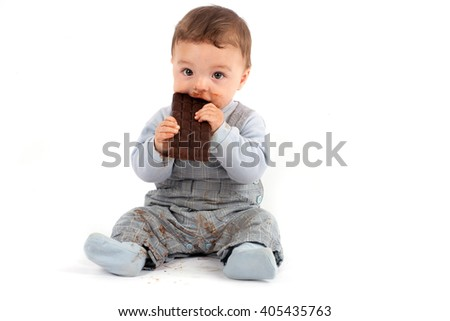 Adorable baby eating a plate of chocolate. Studio isolated on white background. - stock photo