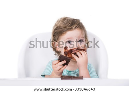 Adorable baby eating chocolate for the first time - stock photo