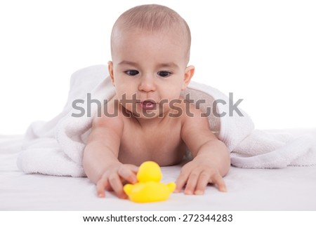 Adorable baby enjoy and looking at yellow duck after bath isoalted - stock photo