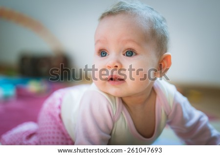 Adorable baby girl crawls on all fours on floor at home. Smiling infant of 6 months playing on ground and looking at camera. Portrait of female child. Vertical, front view. Funny kid goes forward - stock photo