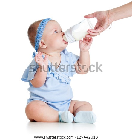 adorable baby girl drinking from bottle with help of mother - stock photo