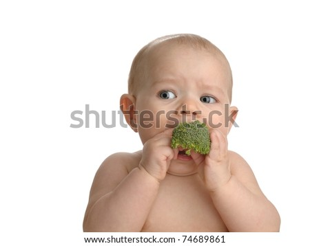 Adorable baby girl eating broccoli isolated on a white background. - stock photo