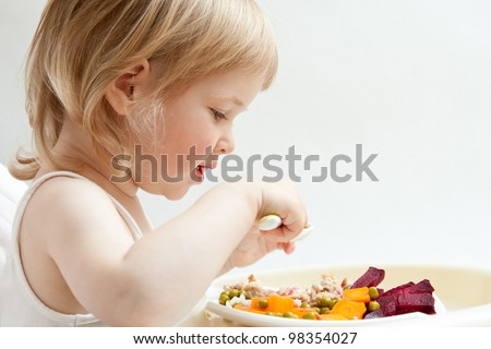 Adorable baby girl eating fresh vegetables; healthy eating for a baby - stock photo