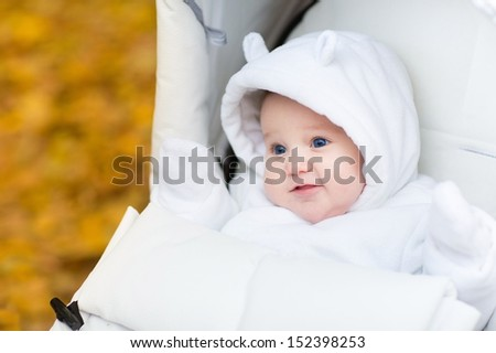 Adorable baby girl in a warm white jacket sitting in a stroller on a walk in an autumn park with yellow foliage - stock photo