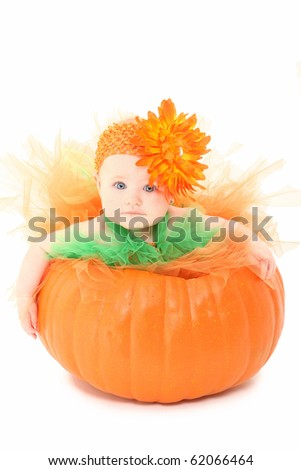 Adorable baby girl in orange and green tutu siting in pumpkin over white background. - stock photo
