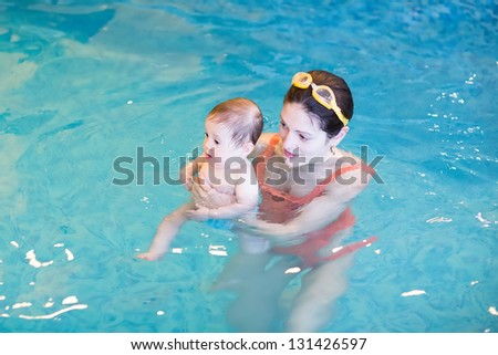 Adorable baby girl in the swimming pool - stock photo