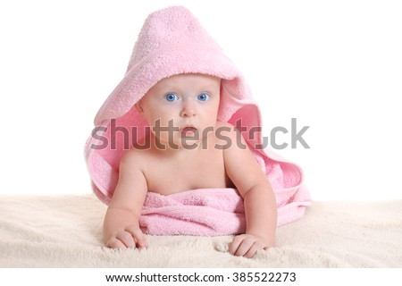 Adorable baby girl, looking out under a pink towel - stock photo