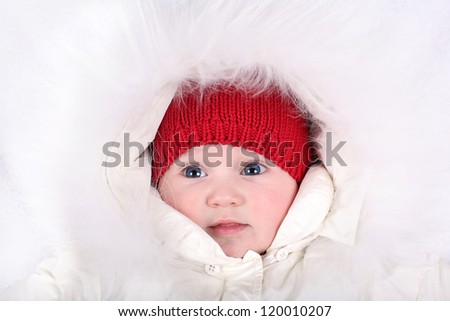 Adorable baby girl looking seriously into the camera wearing a red hat and white fur hood - stock photo