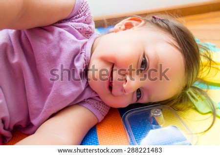 Adorable baby girl lying sideways on floor smiling to camera - stock photo