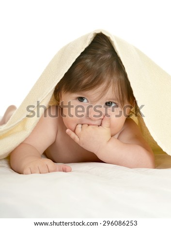 Adorable baby girl lying under blanket on a white background - stock photo