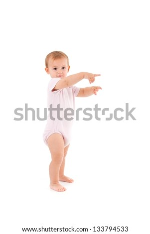 Adorable baby girl making first steps, pointing to distance. - stock photo