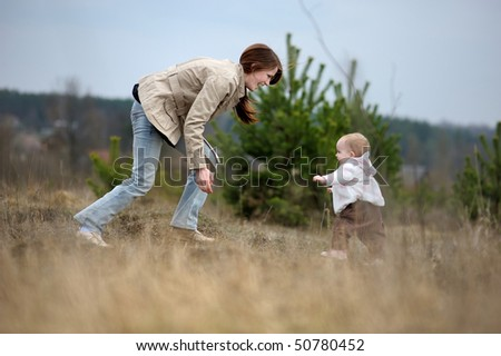 Adorable baby girl making her first steps - stock photo