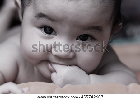 Adorable baby girl .newborn child relaxing and smile close up of face baby .2-6 months two-six months baby healthy concept. - stock photo