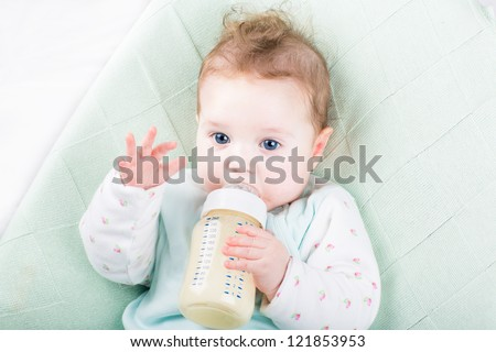 Adorable baby girl on a green knitted blanket drinking milk - stock photo