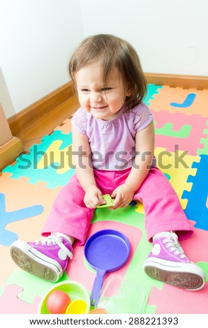 Adorable baby girl playing on floor with a funny facial expression - stock photo
