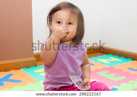 Adorable baby girl sittin on floor and holding her own nose - stock photo