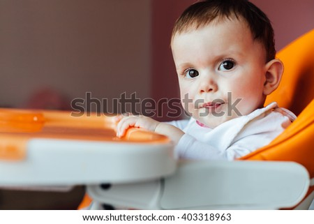 Adorable baby girl sitting in high chair and waiting favorite baby food - stock photo
