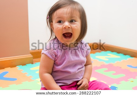 Adorable baby girl sitting on floor and screaming towards camera - stock photo