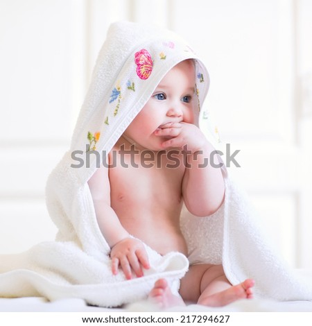 Adorable baby girl sitting under a hooded towel after bath, square - stock photo