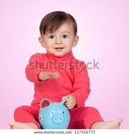 Adorable baby girl sitting with a blue piggy-bank isolated on pink background - stock photo
