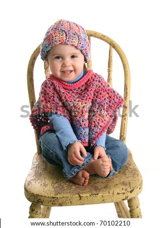Adorable baby girl wearing handmade crochet clothes, a shawl and hat - stock photo
