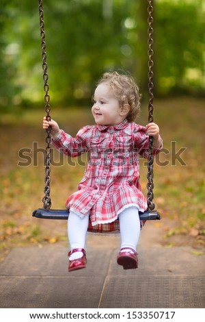 Adorable baby girl with beautiful curly hair wearing a red dress enjoying a swing ride on a playground in a park on a nice sunny autumn day - stock photo