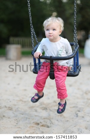 Adorable baby girl with blond curly hair having fun on a swing ride at a playground in a sunny summer park  - stock photo