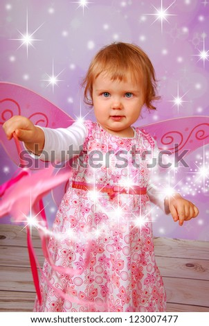 adorable baby girl with fairy wings and wand on pink shining background - stock photo