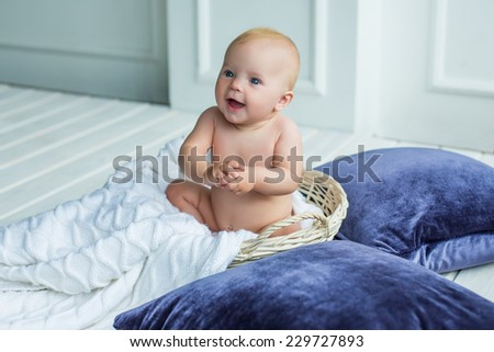 adorable baby girl with fun emotions sitting in basket with blanket at white interior with violet pillows - stock photo