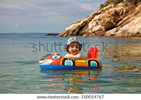 Adorable baby having a sea bath - stock photo
