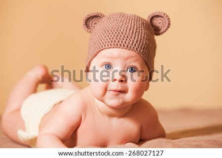 Adorable baby in bear hat lying on the bed - stock photo