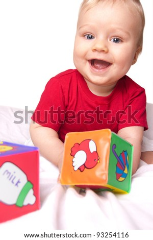 Adorable baby in red shirt playing with bright blocks isolated - stock photo