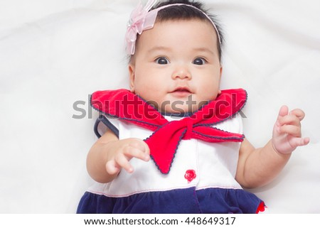 Adorable baby in sailor suit look suspicion on the bed. - stock photo
