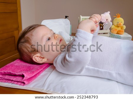 Adorable baby lying playing with a children comb after the change of diaper - stock photo