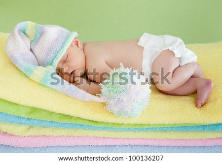 adorable baby newborn in cap sleeping on colorful towels - stock photo