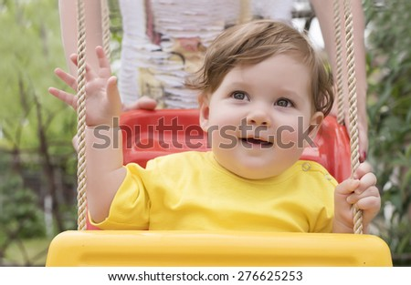 Adorable baby playing in swing - stock photo