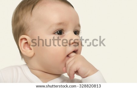 Adorable baby portrait with the hand in the mouth. Cute baby boy looking to the side curious. Isolated on white. - stock photo