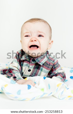 Adorable baby screaming in a plaid shirt. studio photo - stock photo