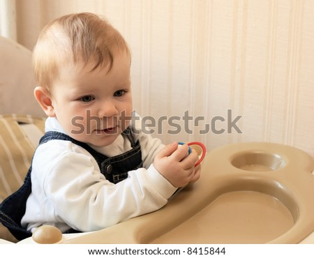 Adorable baby sits at a table - stock photo