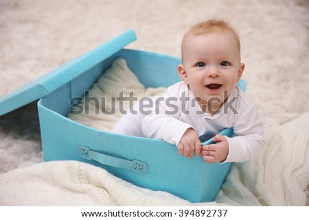 Adorable baby sitting in blue box, close up - stock photo