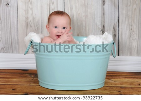 adorable baby sitting in green washtub with blanket - stock photo
