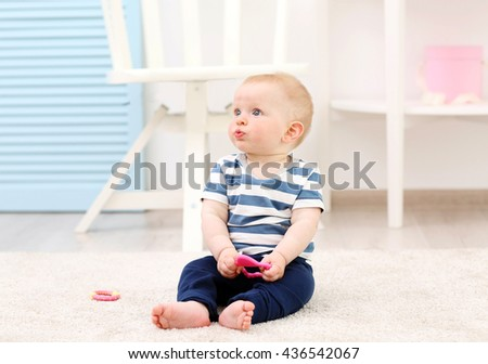 Adorable baby sitting on a carpet - stock photo