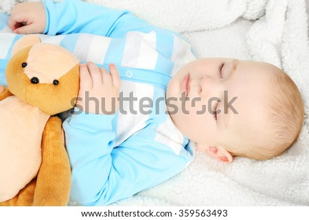 Adorable baby sleeping with teddy bears on sofa in the room, close up - stock photo