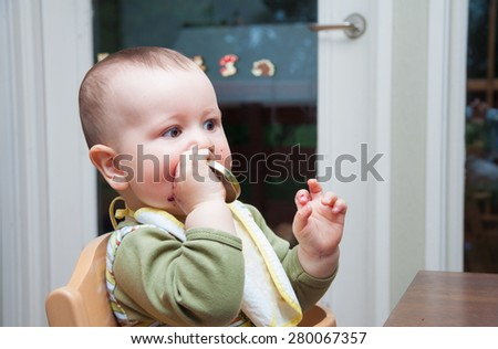 Adorable baby with bib and mouth stained with blueberry jam playing with the cap of the jar - stock photo