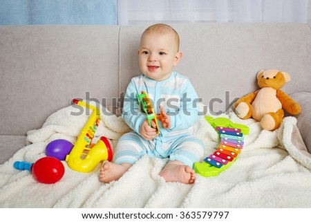 Adorable baby with colourful musical toys on sofa in the room, close up - stock photo