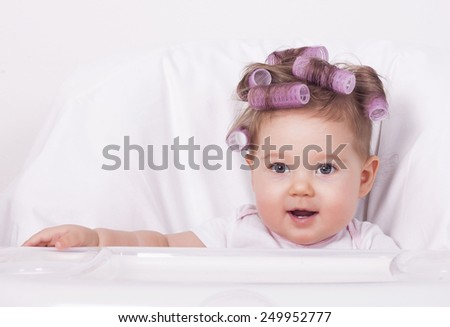 Adorable baby with hair curlers - stock photo
